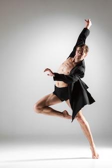 白い壁に若い魅力的なモダンバレエダンサー