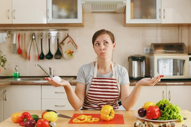 エプロンを着た若い魅力的な物思いにふける女性は、キッチンで鶏とウズラの卵のどちらかを選択します。ダイエットの概念。健康的な生活様式。家で料理。食べ物を用意します。