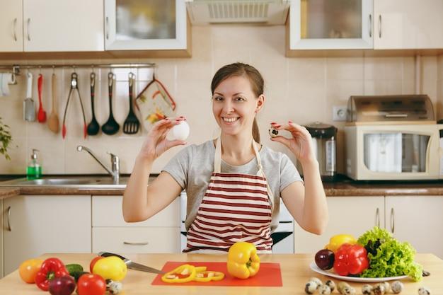 앞치마를 입은 젊고 매력적인 웃는 여성은 부엌에서 닭고기와 메추라기 알 중에서 선택합니다. 다이어트 개념입니다. 건강한 생활. 집에서 요리. 음식을 준비하다.