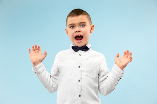 Молодой привлекательный мальчик-подросток выглядит удивленным изолированным на синем