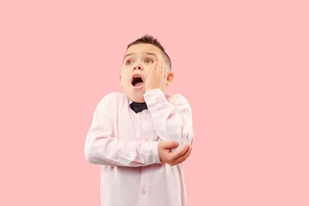 Молодой привлекательный мальчик-подросток выглядит удивленным изолированным на розовом
