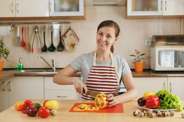 エプロンを着た若い魅力的な女性は、キッチンでナイフを使ってサラダ用の野菜を切ります。ダイエットの概念。健康的な生活様式。家で料理。食べ物を用意します。