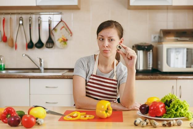 エプロンの若い魅力的な女性は、キッチンでウズラの卵を手に持っています。ダイエットの概念。健康的な生活様式。家で料理。食べ物を用意します。