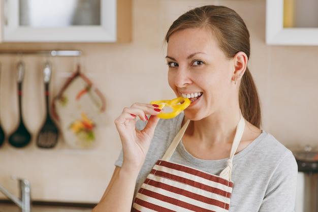 エプロンを着た若い魅力的な女性は、キッチンで黄ピーマンを味わいます。ダイエットの概念。健康的な生活様式。家で料理。食べ物を用意します。