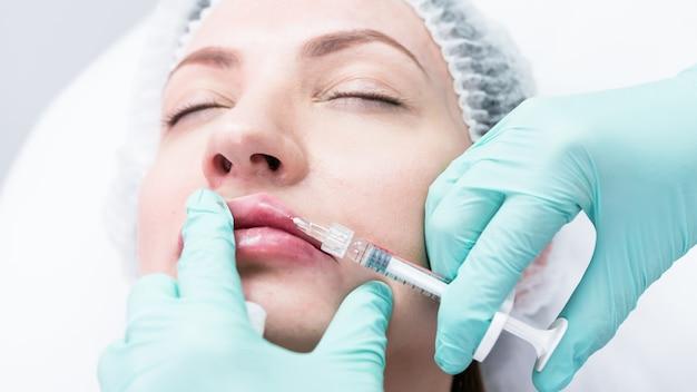 Молодой врач косметолог готовится сделать инъекцию в женские губы