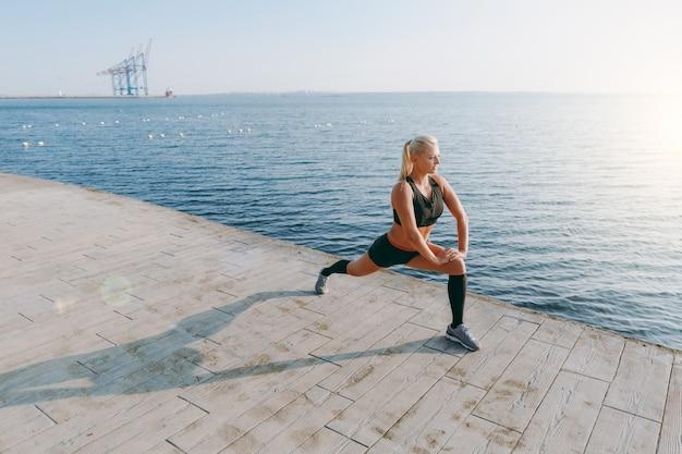 Молодая красивая спортивная девушка с длинными светлыми волосами в черной одежде делает растяжку на восходе солнца над морем