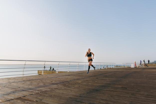 Молодая красивая спортивная девушка с длинными светлыми волосами в черной одежде бежит на восходе солнца над морем