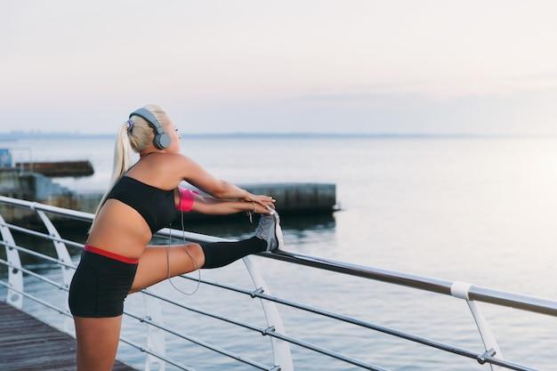 音楽を聴き、海の上の日の出でストレッチをしているヘッドフォンで長いブロンドの髪を持つ若い美しい運動少女