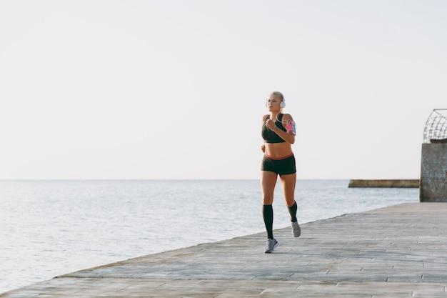 Молодая красивая спортивная девушка с длинными светлыми волосами в наушниках слушает музыку и бежит на восходе солнца над морем