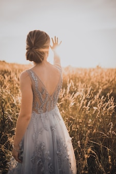 背中が開いた灰色のドレスを着た若い美しい少女は、手を上げて太陽の光を閉じます。