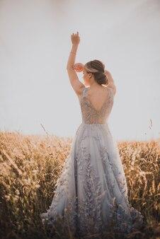 背中が開いた灰色のドレスを着た若い美しい少女は彼女の手を上げた
