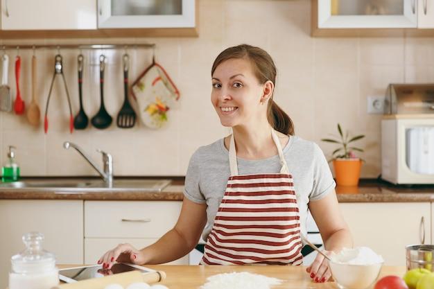 Молодая красивая счастливая женщина ищет рецепт тортов в таблетке на кухне. готовим дома. готовить пищу.