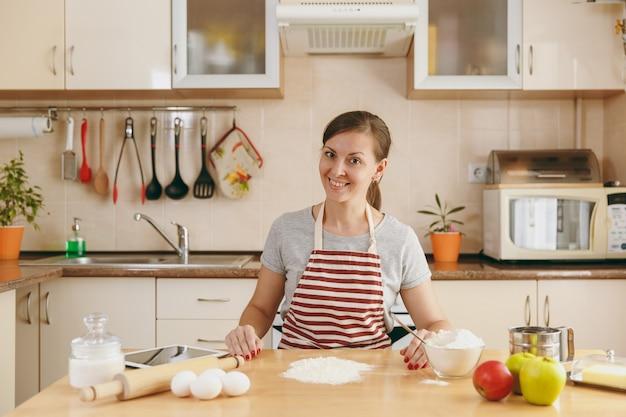 Молодая красивая счастливая женщина готовит тесто для тортов с таблеткой на столе на кухне. готовим дома. готовить пищу.