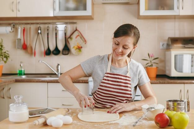 젊고 아름다운 행복한 여성은 식탁에 밀가루를 얹고 부엌에서 만두를 만들기 위해 반죽 원에서 유리를 잘라냅니다. 집에서 요리. 음식을 준비하다.