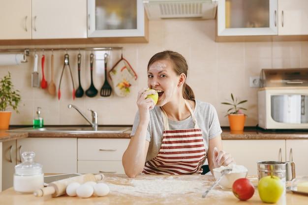 젊고 아름다운 행복한 여성이 식탁에 밀가루를 얹고 부엌에서 케이크를 준비하려고 합니다. 집에서 요리. 음식을 준비하다.