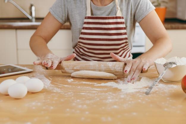 젊고 아름다운 행복한 여성이 밀가루와 태블릿을 들고 탁자에 앉아 롤링 핀으로 반죽을 굴리고 부엌에서 케이크를 준비하려고 합니다. 집에서 요리. 음식을 가까이서 준비하십시오.