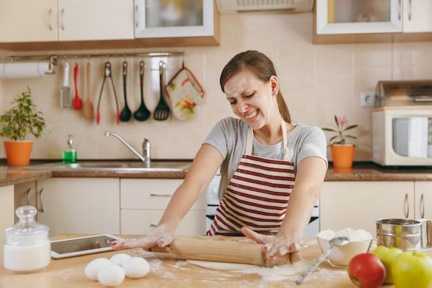 젊고 아름다운 행복한 여성이 밀가루와 태블릿을 들고 탁자에 앉아 롤링 핀으로 반죽을 굴리고 부엌에서 케이크를 준비하려고 합니다. 집에서 요리. 음식을 준비하다.