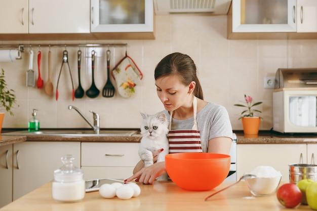 Молодая красивая счастливая женщина с белым персидским котом ищет рецепт пирожных в планшете на кухне. готовим дома. готовить пищу.