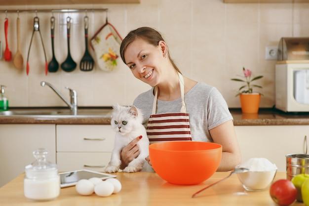 Молодая красивая счастливая женщина с белым персидским котом готовит тесто для тортов с таблеткой на столе на кухне. готовим дома. готовить пищу.
