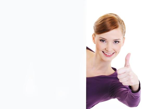 Молодая красивая женщина радости смотрит из-за пустого белого