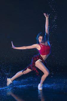 Молодая красивая современная танцовщица танцует под каплями воды в синей аквастудии