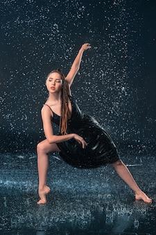 물 방울에서 춤추는 젊은 아름다운 현대 댄서