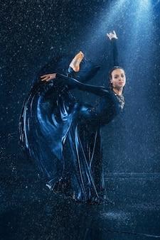 水滴の下で踊る若い美しいモダンダンサー