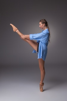 스튜디오 회색 배경에 포즈 블루 셔츠에 젊은 아름 다운 현대적인 스타일 댄서