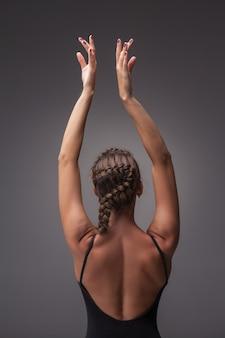 スタジオの灰色の背景でポーズをとる若い美しいモダンなスタイルのダンサー。後ろからの眺め