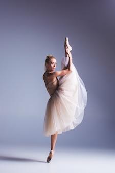 Молодая красивая танцовщица современного стиля позирует на сером фоне студии
