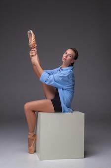 スタジオの灰色の背景に白い立方体でポーズをとる若い美しいモダンなスタイルのダンサー