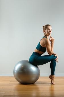 Молодая, красивая, спортивная девушка делает упражнения на фитболе в тренажерном зале на серой поверхности
