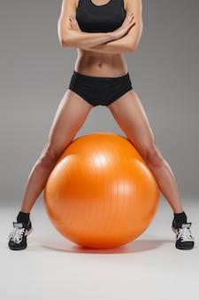 Fitball에서 운동을하는 젊고 아름다운 스포츠 소녀