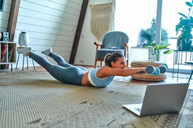 Молодая красивая спортивная девушка в леггинсах и топе делает упражнения с ганетли. здоровый образ жизни. женщина занимается спортом с ноутбуком дома.