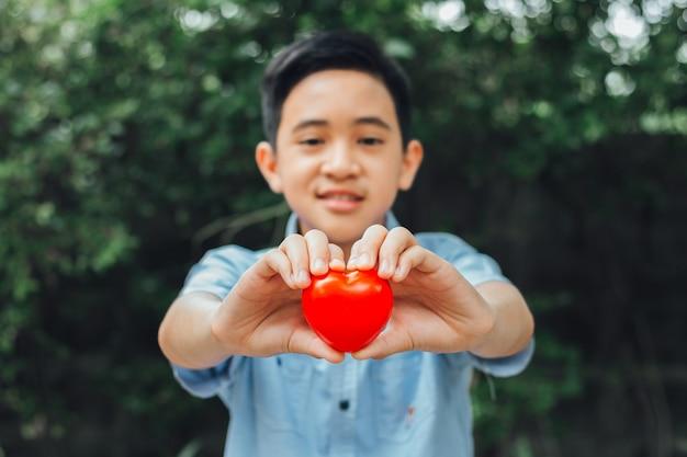 Молодая пара мальчика показывает мини красное сердце и улыбается, концепция любви