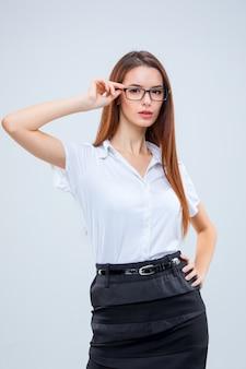 灰色の背景上の眼鏡の若いビジネス女性