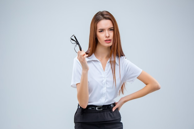 Молодая деловая женщина в очках на сером пространстве