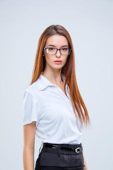Молодая деловая женщина в очках на сером