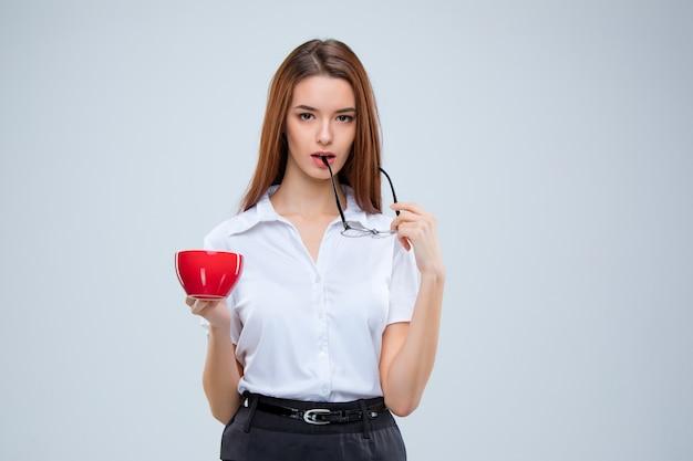 灰色の背景に赤のコーヒーカップとガラスの若いビジネス女性