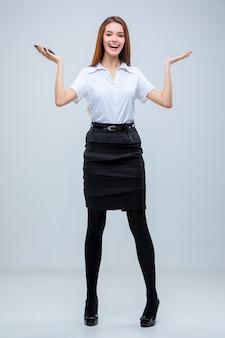 灰色の壁に若いビジネス女性