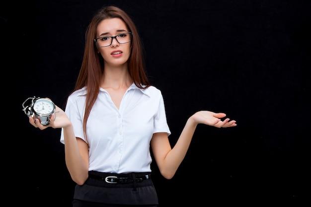 黒の目覚まし時計を持つ若いビジネス女性
