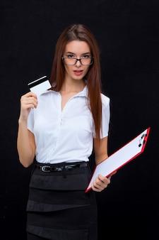 クレジットカードと灰色のノートのためのタブレットを持つ若いビジネス女性