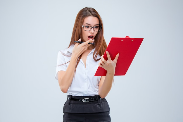 Молодая деловая женщина с ручкой и планшетом для заметок на серой стене