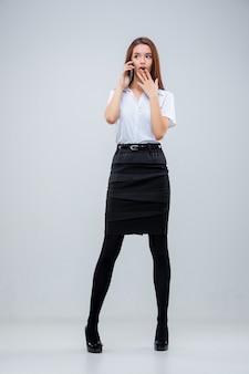 Молодая деловая женщина с телефоном на сером пространстве