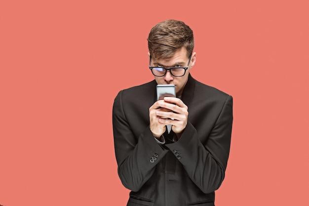 Молодой кавказский бизнесмен в очках на фоне красной студии разговаривает по мобильному телефону