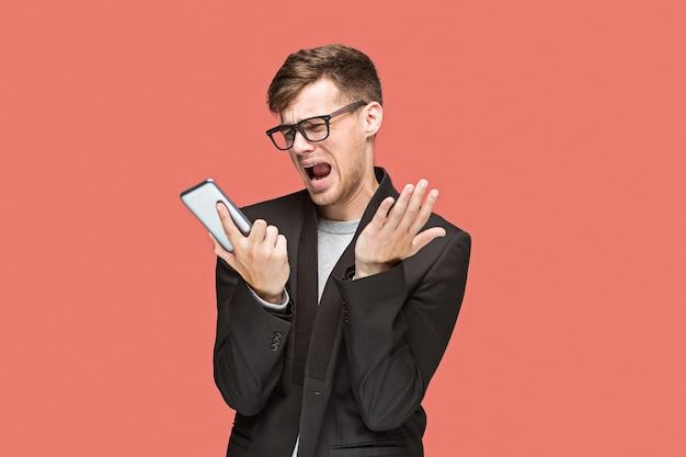携帯電話で話している赤いスタジオでメガネの若い白人実業家