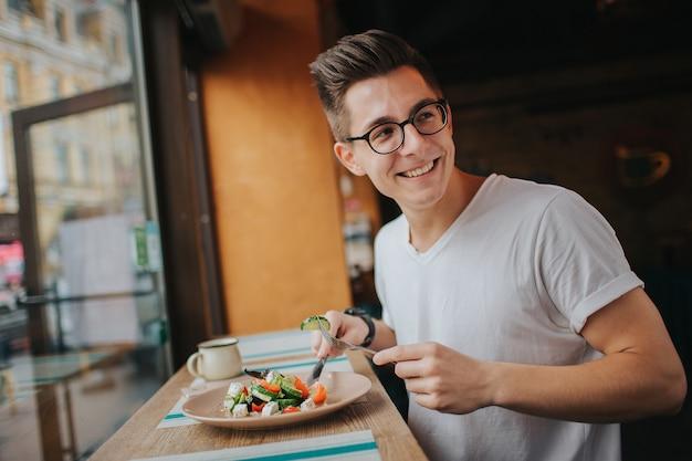 ヘルシーなサラダを食べる眼鏡の若い白人男。