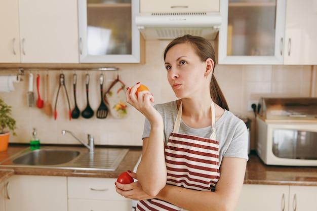 エプロンを着た若い混乱した物思いにふける女性は、台所で赤または黄色のトマトを選ぶことにしました。ダイエットの概念。健康的な生活様式。家で料理。食べ物を用意します。