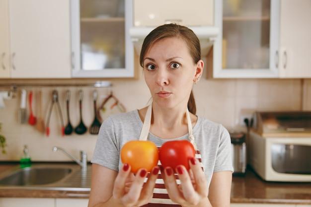 エプロンを着た若い混乱した女性は、台所で赤または黄色のトマトを選ぶことにしました。ダイエットの概念。健康的な生活様式。家で料理。食べ物を用意します。