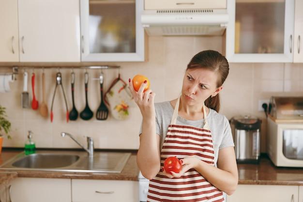 앞치마를 입은 혼란스러운 젊은 여성은 부엌에서 빨간색이나 노란색 토마토를 선택하기로 결정합니다. 다이어트 개념입니다. 건강한 생활. 집에서 요리. 음식을 준비하다.